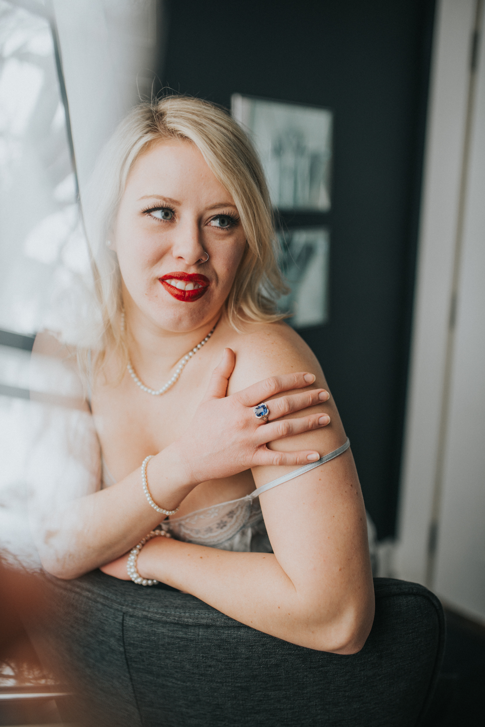 woman in red lipstick and vintage lingerie wearing a vintage ring durring her boudoir photography session in st paul