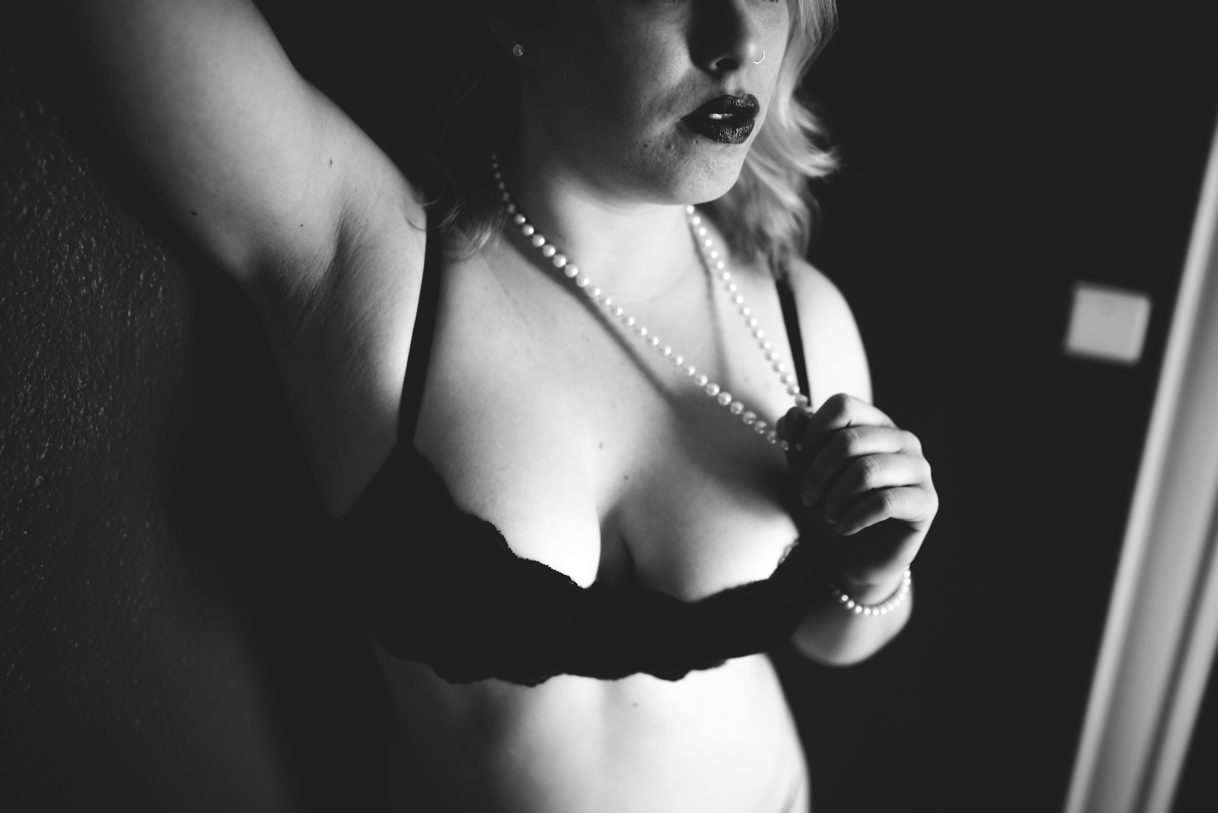 black and white boudoir photo of a woman holding her pearls. Boudoir photography by st paul photographer The Hawk & Sparrow