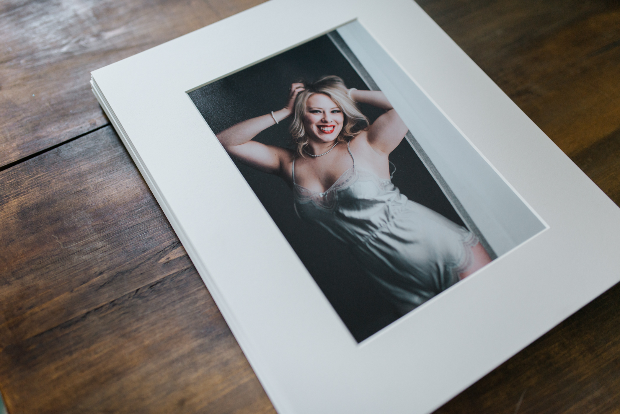 Mounted and matted boudoir portrait of smiling woman with red lipstick and blond hair. Photograph by St Paul Boudoir Photographer Madelin Zaycheck