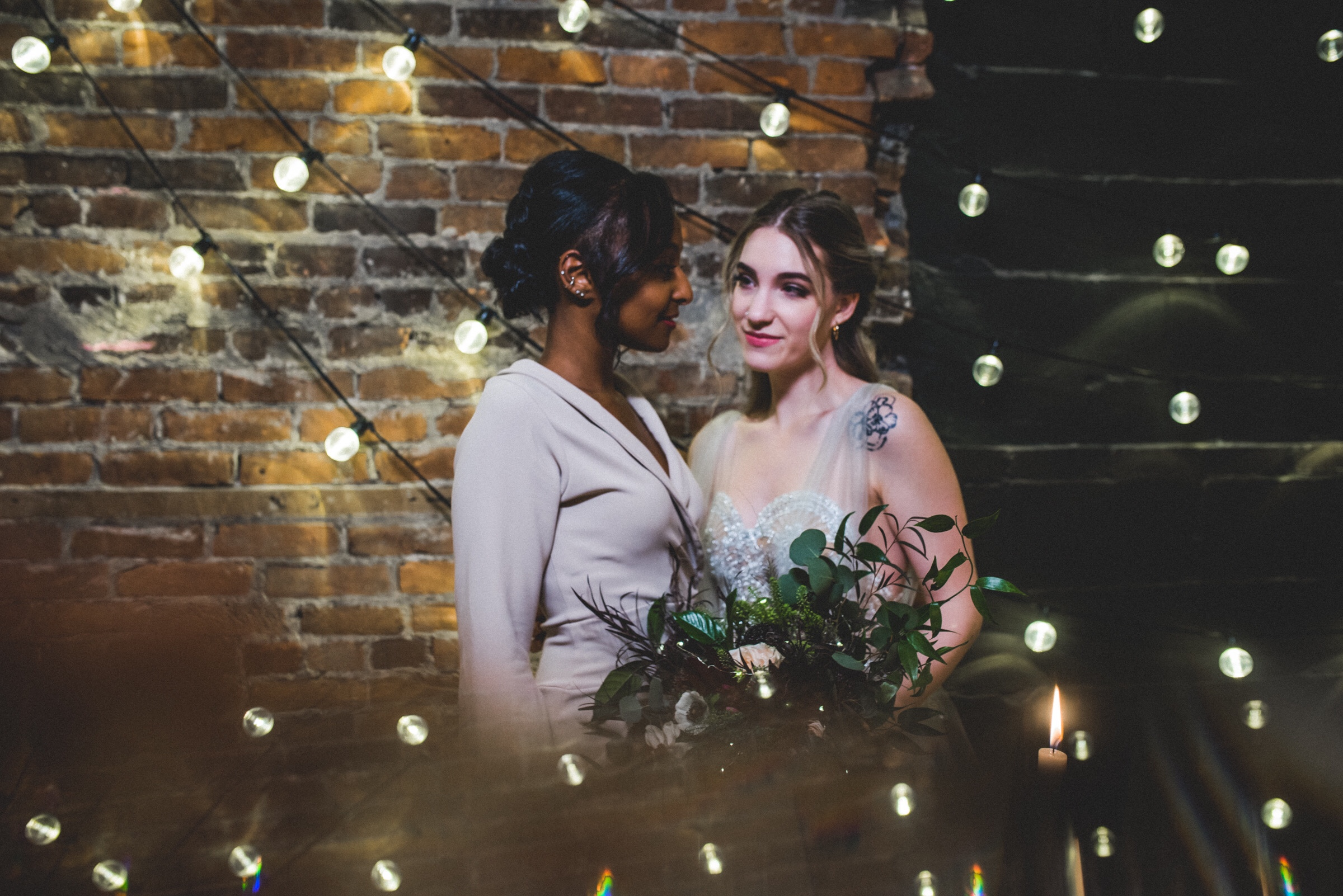 Same sex bridal couple surrounded by lights at minnesota wedding venue The loft at studio J. Portrait captured by minnesota wedding photographer Madelin Zaycheck of the Hawk and Sparrow using a prism for reflection of the lights